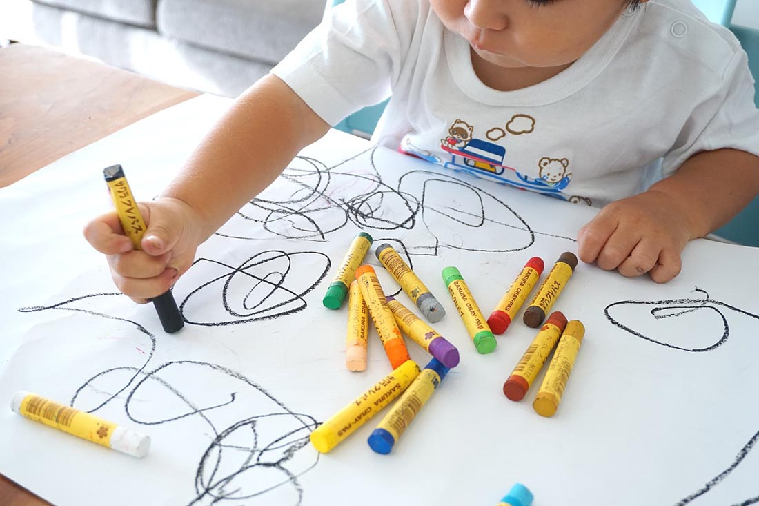 The child draws with wax colors, photo credit Oekaki Oe