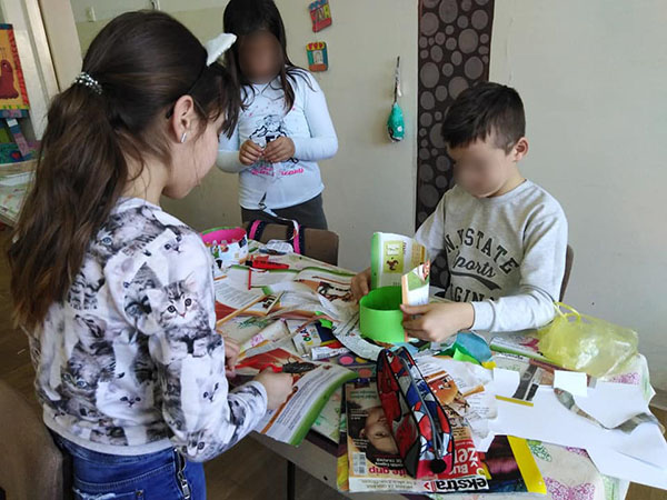 Children make hats from collage paper