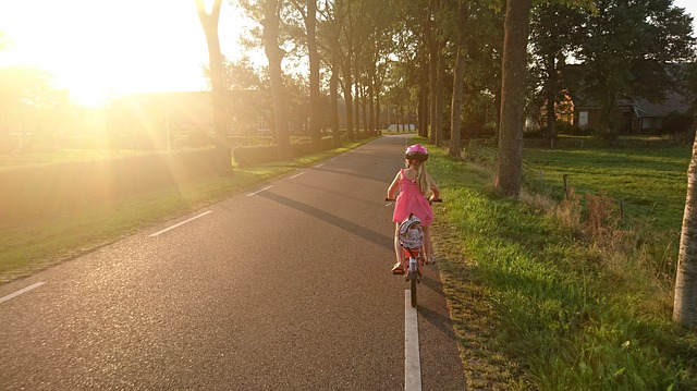 Girl ride a bicycle to school, photo credit Skitterphoto