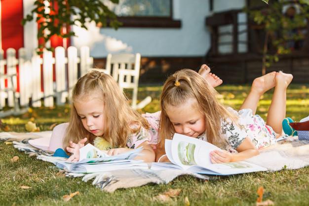 Girls read books on the grass