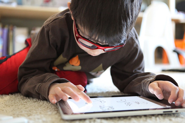 The boy uses a touch-screen tablet