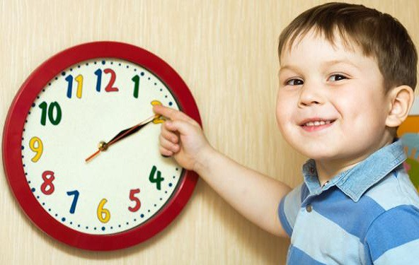 The child points to the clock