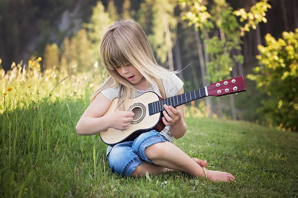 A child playing gitar, photo credit Pezibear