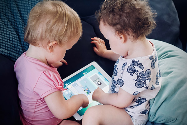 Two toddlers sitting on sofa while using tablet computer,photo credit Jelleke Vanooteghem, Unsplash