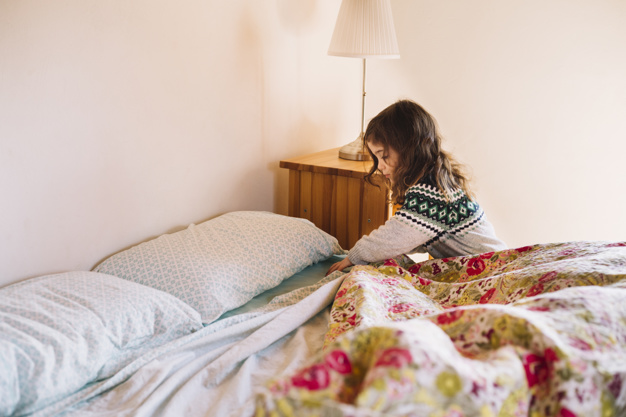 The girl sets the bedding on the bed , Freepik