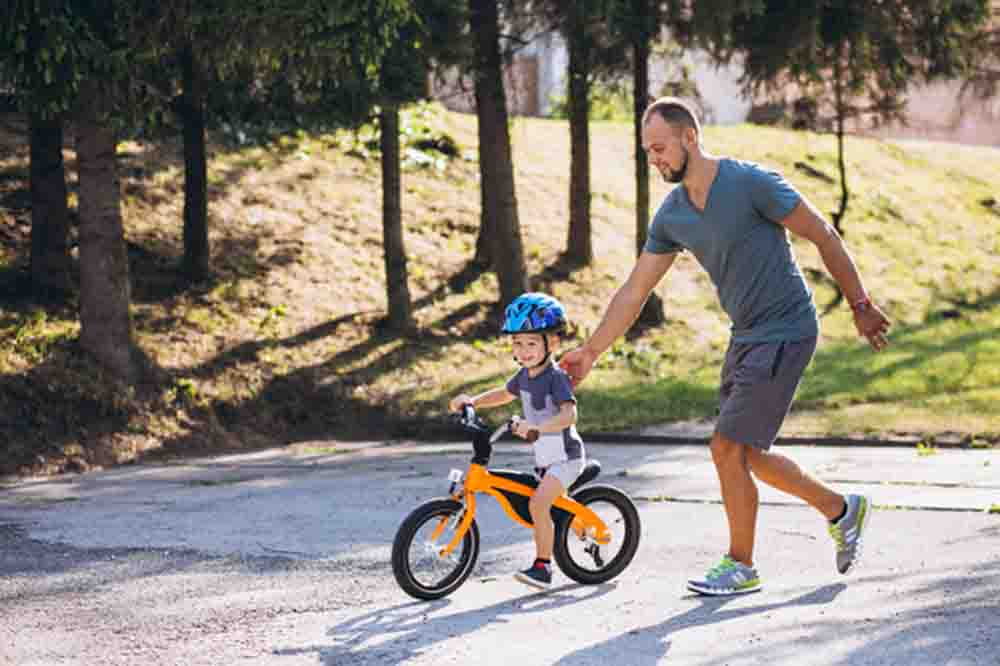 Father teachs his little son to ride a bicycle, photo credit sanivpetro
