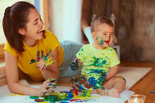 Mother with son painting big paper with their hands, photo credit Freepik