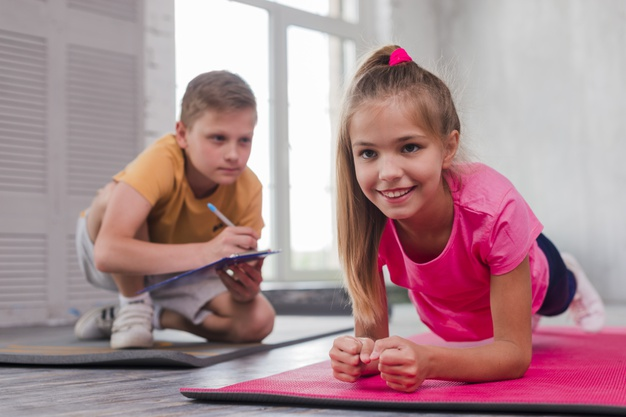 Boy writing number while girl exercising, Freepik