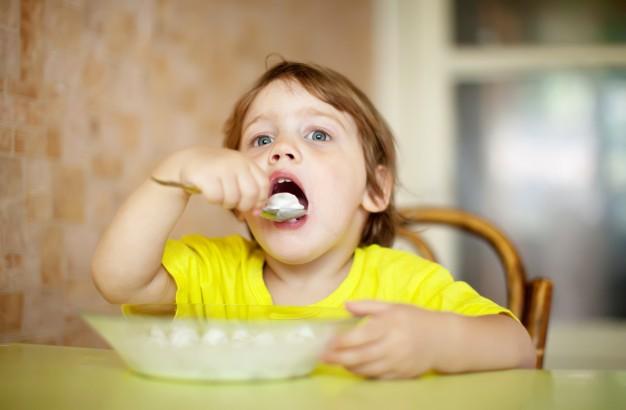 The child eats alone, Freepik