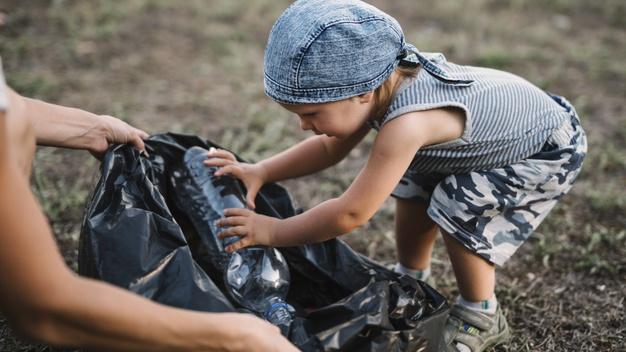 Little kid putting plastic bottle in a trash bag